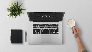 Opgeruimd bureau met laptop, pennen, plant en een kop koffie
